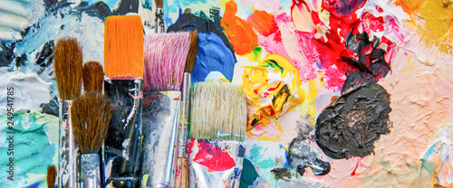 Photo Used paint brushes on a colorful painter palette