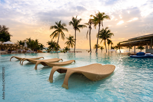 Obraz na plátně luxury swimming pool on sea view and chair in hotel resort with sunrise time