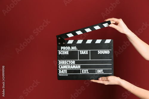 Wallpaper Mural Female hands with cinema clapperboard on color background