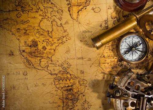Top view of vintage navigation equipment on old world map.