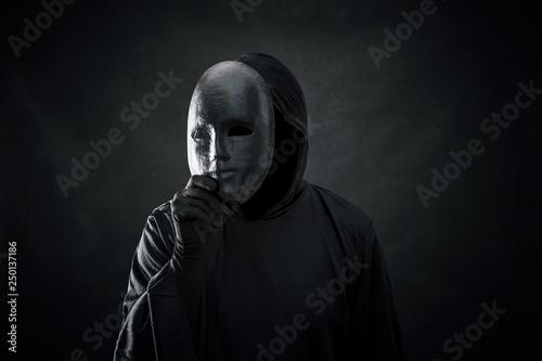 Fototapeta premium Straszna postać w płaszczu z kapturem z maską w ręku