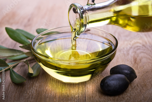 Fotografia Bowl with olive oil on wooden table