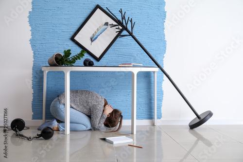Slika na platnu Young woman hiding under table during earthquake