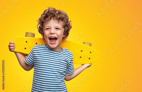 Fotografia, Obraz Bright curly boy with colorful longboard