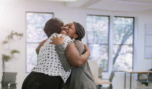 Fotografiet Two female black african freelancers embraced in a friendly hug in a modern co-w