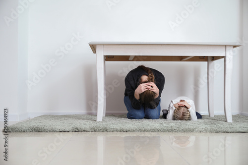Tableau sur Toile Mother with daughter under table during earthquake indoors
