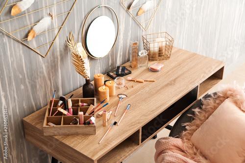 Fototapeta Dressing table with set of cosmetics near grunge wall