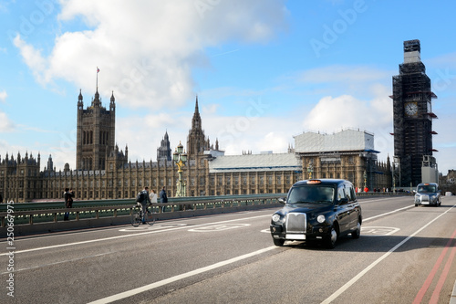 Canvas Print Black cabs drive on the London street with illuminated taxi sign