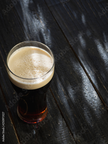 Wallpaper Mural Cold glass of dark stout beer on wooden table