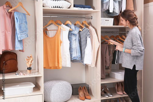 Fotografia Woman choosing outfit from large wardrobe closet with stylish clothes, shoes and
