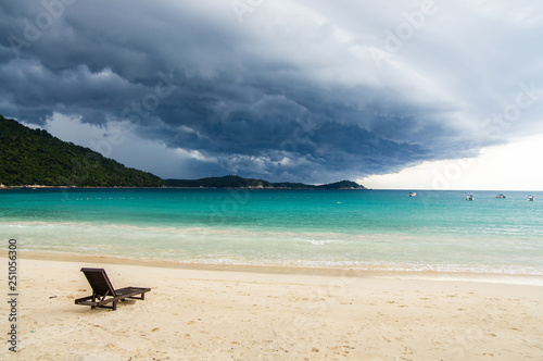 Photographie Lonely chaise longue on a deserted beach, against a background of approaching tropical thunderstorm