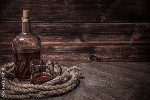 Fotografia pirates bottle and glass on atone table, old rope, rum oe whiskey in transparent