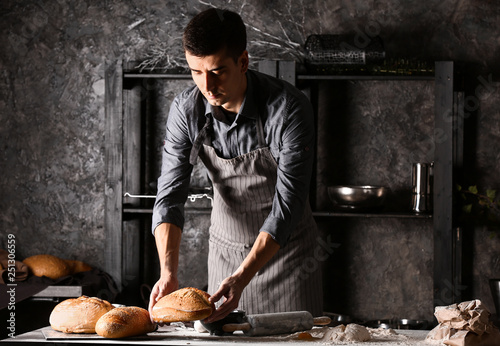 Fotografia Young man with freshly baked bread in kitchen