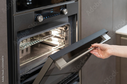 Woman hand opening built-in oven in black kitchen cabinet Fototapet