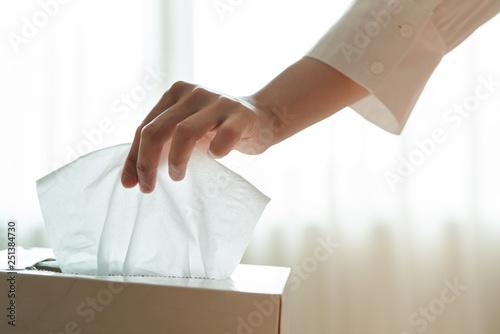 Leinwand Poster women hand picking napkin/tissue paper from the tissue box