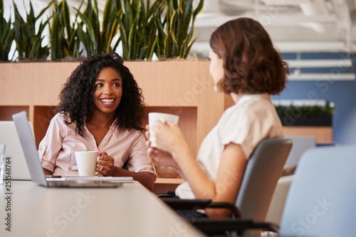 Fotografija Two Businesswomen Working At Table In Modern Open Plan Office Drinking Coffee To