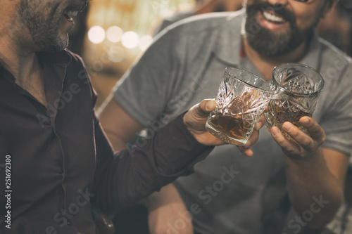 Fotografija Close up of two unrecognizable men clinking crystal glasses with strong alcohol