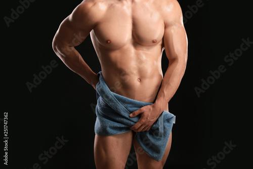 Muscular sexy bodybuilder with towel on dark background