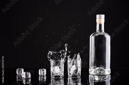 Fotografia bottle of vodka with glasses and splashes on a black background
