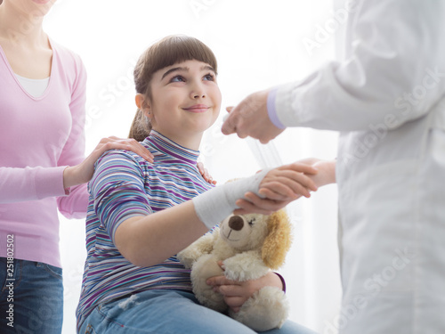 Doctor wrapping a girl's injured wrist with a bandage Fototapet