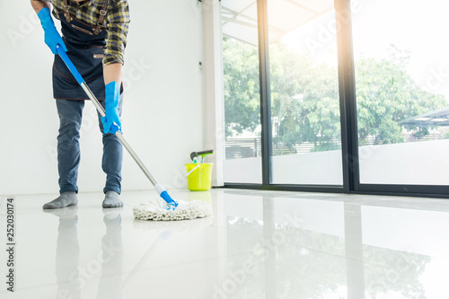 Obraz na płótnie Young housekeeper cleaning floor mobbing holding mop and plastic bucket with brushes, gloves and detergents in the leaving room house floor helping his wife