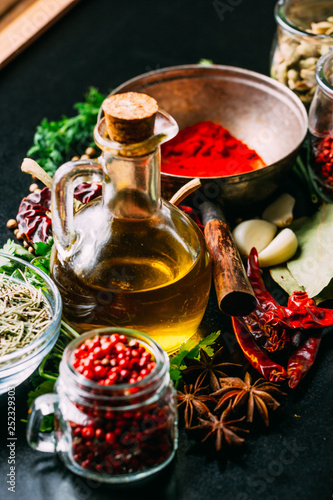 Assorted spices and herbs and bottle of oil placed on wooden tabletop
