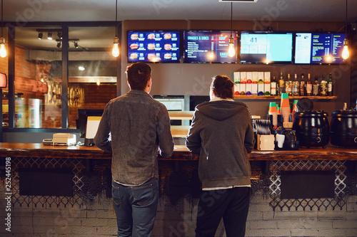 Obraz na plátně Two men choose food in a fast food restaurant.