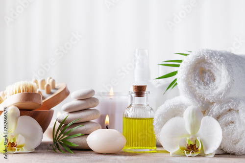 Spa, beauty treatment and wellness background with massage pebbles, orchid flowers, towels, cosmetic products and burning candles.