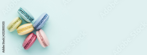 Obraz na plátně Six colorful macarons on turquoise background