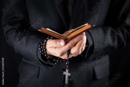 Fotografia Hands of a christian priest dressed in black holding a crucifix and reading New Testament book