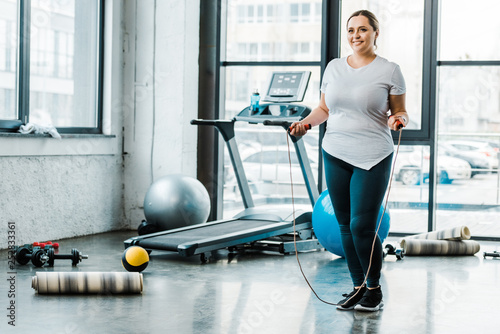 Carta da parati cheerful plus size woman standing with jumping rope in gym