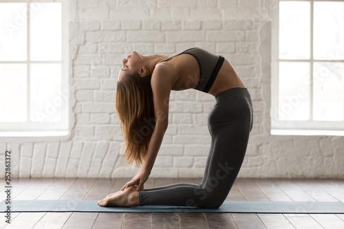 Fényképezés Young woman practicing yoga, standing in Ustrasana pose, Camel exercise