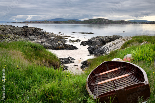Fototapeta Rocky shore of Isle of Iona with beached boat with Fionnphort Isle of Mull and m