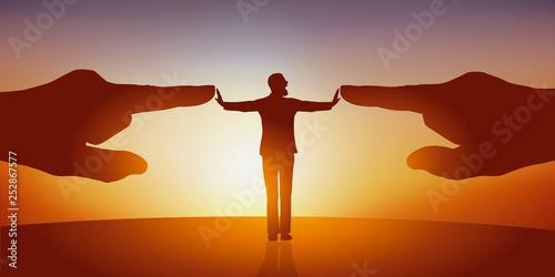 Obraz na plátně Concept de l'opposition avec un homme les bras écartés qui repousse symboliquement deux énormes mains le montrant du doigt pour le désigner comme bouc émissaire