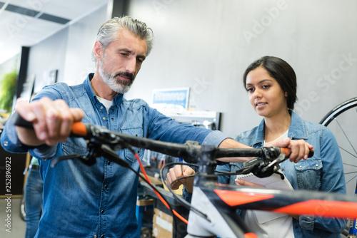 female apprentice repairing a bike in workshop