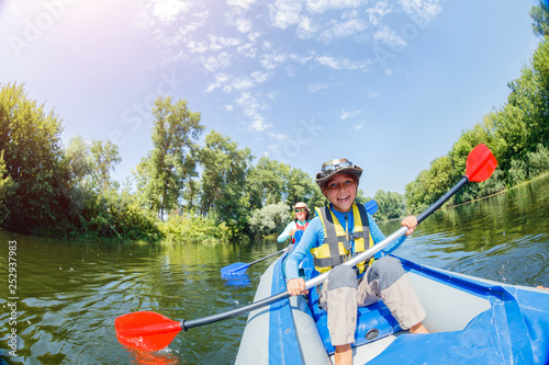 Tableau sur Toile Happy boy kayaking on the river on a sunny day during summer vacation