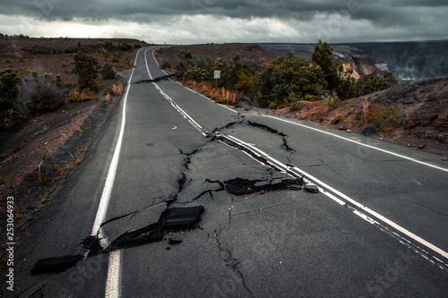 Slika na platnu Damaged asphalt road (Crater Rim Drive) in the Hawaii Volcanoes National Park after earthquake and eruption of Kilauea (fume at upper right) volcano in May 2018