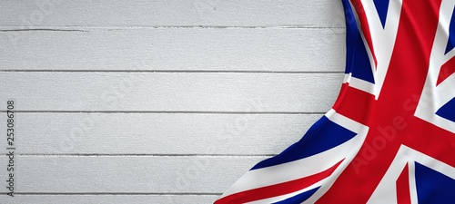 Foto United kingdom flag, on top of white wood. Wrinkled fabric.