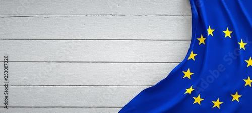 Fotografia European union flag, on top of white wood. Wrinkled fabric.