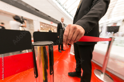 Photo Security hand fastens a red tape closing the passage