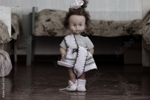 Canvas Print The doll stands between the beds in the bedroom of the orphanage