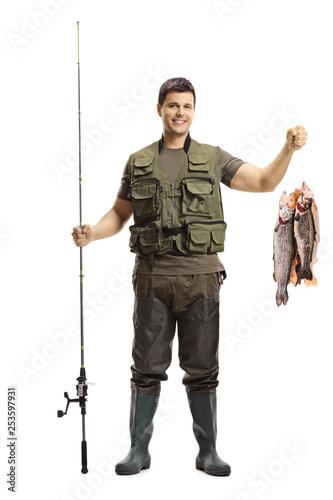 Valokuvatapetti Young fisherman posing with a fishing rod and fish