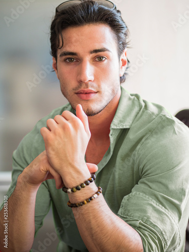 Photographie Attractive young man indoors wearing a shirt and beaded bracelets