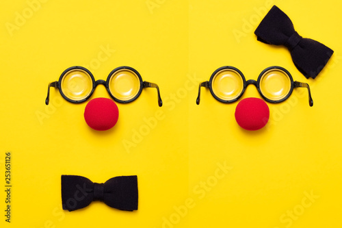 Photo Funny glasses, red clown nose and tie lie on a colored background, like a face