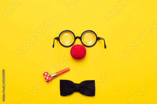 Billede på lærred Funny glasses, red clown nose and tie lie on a colored background, like a face