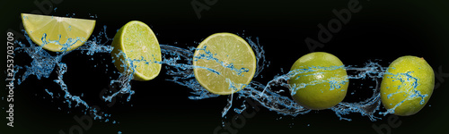 Fotografia tasty fruit - lime in water on an isolated green and black background