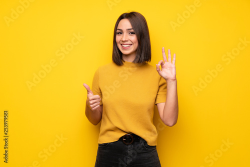 Young woman over yellow wall showing ok sign with and giving a thumb up gesture