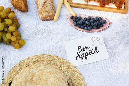 Fényképezés straw hat lay on a white picnic blanket next to nameplate bon apetit bright summer day background