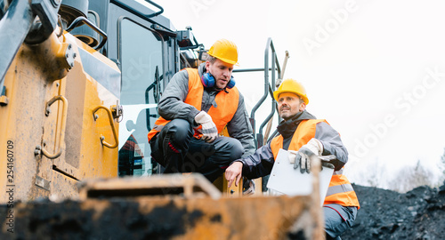 Photo Foreman showing worker in open-cast mining pit direction
