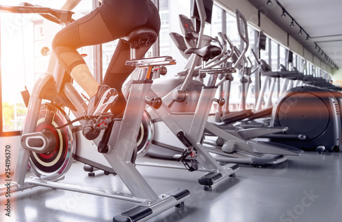 Fotografie, Obraz Exercise bike cardio workout at fitness gym of woman taking weight loss with machine aerobic for slim and firm healthy in the morning